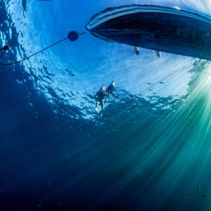 Boat Ship From Underwater Blue Ocean With Sun Rays